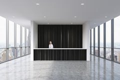 Un área de recepción en una oficina limpia brillante moderna con un recepcionista hermoso en ropa formal Ventanas panorámicas eno Fotografía de archivo libre de regalías