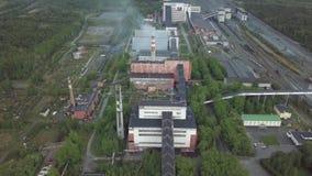 Un área enorme de la planta industrial con los edificios viejos rodeados por la opinión aérea del bosque almacen de metraje de vídeo