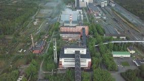 Un área enorme de la planta industrial con los edificios viejos rodeados por la opinión aérea del bosque metrajes