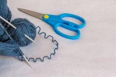 Un écheveau de fil pour le tricotage, les aiguilles de tricotage et ciseaux, Photo libre de droits