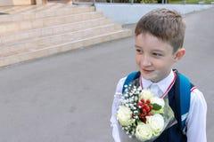 Un écolier avec un bouquet des roses blanches dans le sien main extérieure photo libre de droits