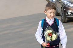 Un écolier avec un bouquet des roses blanches dans le sien main extérieure images stock