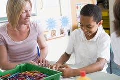 Un écolier et son professeur dans une classe d'art Image stock