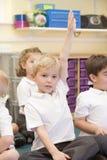 Un écolier soulève sa main dans une classe primaire photo stock