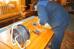 Un électricien d'homme travaillant des travaux, rassemble le circuit électrique d'un grand réverbère blanc avec des fils, un rela photos libres de droits
