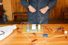 Un électricien d'homme travaillant des travaux, rassemble le circuit électrique d'un grand réverbère blanc avec des fils, un rela photo libre de droits