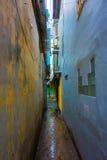 Un étroit, une allée colorée et foncée entre deux bâtiments avec les fenêtres ouvertes et des volets Photo stock