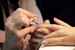 Un étudiant aux cours de formation de la manucure applique la coquille de gel de couleur or rose de couleur photo stock