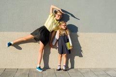 Un étudiant de lycée et un étudiant d'école primaire posent pour un appareil-photo Photos stock