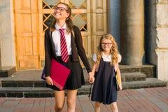 Un étudiant de lycée et un étudiant d'école primaire tiennent des mains près des portes de l'école Photo stock