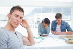 Un étudiant de regard sérieux avec sa main sur sa tête examine t Photographie stock libre de droits