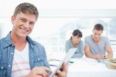 Un étudiant de sourire à l'aide de son comprimé avec ses amis dans le backg Image stock