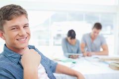 Un étudiant de sourire avec le sien main près de son coffre comme il regarde dans Image stock