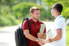Un étudiant universitaire heureux de rencontrer son ami et puis de se serrer la main Images stock
