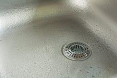 Un évier avec Waterdrops et tamis de drain de Chrome Image stock