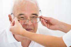 Un óptico Helping Male Patient con las nuevas lentes Imagenes de archivo