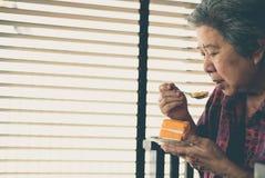 Un aîné plus âgé mangeant le gâteau orange au café la femme agée asiatique s'asseyent Images stock