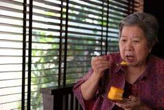 Un aîné plus âgé mangeant le gâteau orange au café la femme agée asiatique s'asseyent Photos libres de droits