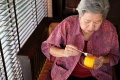 Un aîné plus âgé mangeant le gâteau orange au café la femme agée asiatique s'asseyent Images libres de droits