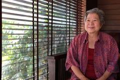 Un aîné plus âgé se reposant à la maison femme agée heureuse s'asseyant dans le liv Images libres de droits