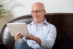 Un aîné regarde un comprimé numérique Images libres de droits