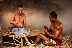 Un aîné tissant le rotin sec et un homme toilettant un coq pour la vie de campagne Concept traditionnel rural thaïlandais asiatiq Image libre de droits
