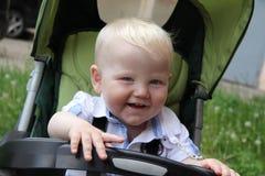 Un años de muchacho con el carro de bebé Imagenes de archivo