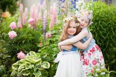Un abbraccio di due sorelline nel giardino immagine stock libera da diritti