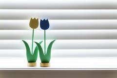 Un abbraccio di legno di due tulipani nell'incandescenza morbida di luce del giorno di una tonalità di finestra Fotografia Stock Libera da Diritti