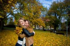 Un abbraccio piacevole di due ragazze allegro nel parco di autunno Fotografia Stock Libera da Diritti