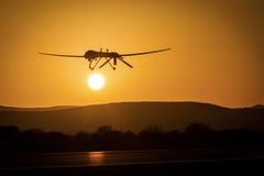 Un abejón sin tripulación de paso bajo en puesta del sol foto de archivo libre de regalías