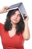 Un abook femminile della holding dell'adolescente sulla sua testa Immagine Stock