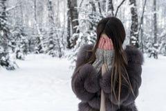 Un abrigo de pieles de la muchacha cubre su cara con sus palmas Foto de archivo libre de regalías