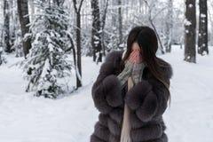 Un abrigo de pieles de la muchacha cubre su cara con sus palmas Fotos de archivo