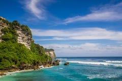 Un acantilado, un agua azul y un cielo claro Foto de archivo