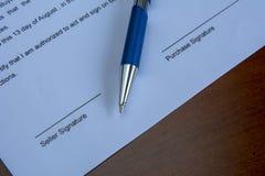 Un accordo di acquisto con una penna su uno scrittorio Fotografia Stock Libera da Diritti