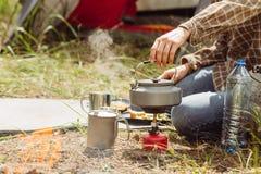 Un'acqua bollente della persona sopra una stufa del propano per produrre tè immagini stock