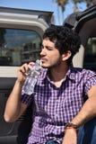 Un'acqua in bottiglia bevente bella del giovane all'aperto fotografie stock libere da diritti