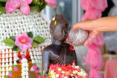Un'acqua di versamento del fiore della mano maschio su una statua del monaco al tempio di Buddha per il festival di Songkran in T fotografie stock