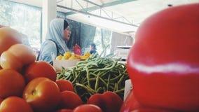 Un acquisto asiatico della donna ad un mercato delle verdure Fotografie Stock Libere da Diritti