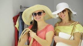Un acquisto di due donne che prova i vestiti divertenti vicino allo specchio Bei giovani clienti nella stanza di montaggio archivi video