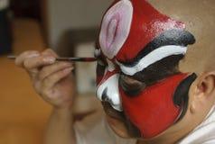 Un actor chino de la ópera está pintando su cara Foto de archivo libre de regalías