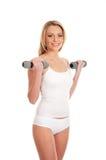 Un addestramento biondo della donna di misura in vestiti bianchi Fotografia Stock