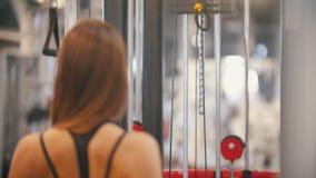 Un addestramento della donna dell'atleta nella palestra - tirando le maniglie collegate per pesare i pezzi - muscoli e mani di po stock footage