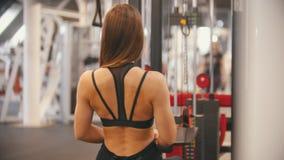 Un addestramento della donna dell'atleta nella palestra - tirando le maniglie collegate per pesare - muscoli e mani di pompaggio  archivi video