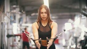 Un addestramento della donna dell'atleta nella palestra - tirando le maniglie - muscoli di pompaggio del petto stock footage