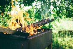 un addetto alla brasatura con il legno di combustione, cucinante sulla campagna, sera di estate all'aperto immagine stock