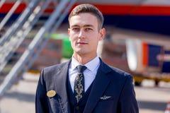 Un administrador hermoso y valeroso vestido en el uniforme azul marino oficial de las líneas aéreas de Aeroflot en el campo de av imagen de archivo