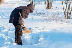 Un adolescent creusant une pelle à neige en bois images stock