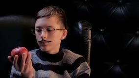Un adolescent en verres avec a coller-sur la moustache, utilisant un chandail, s'assied dans une chaise en cuir noire et regarde  photos stock